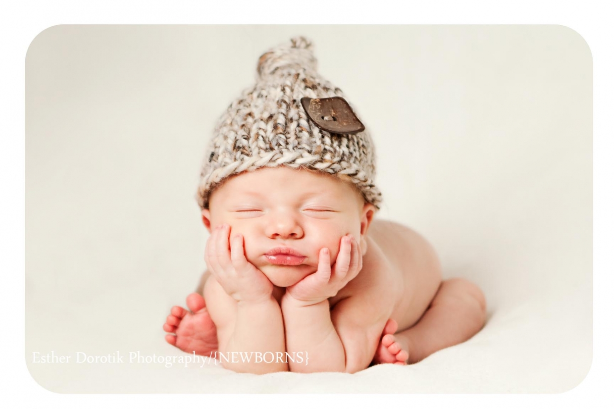 baby with hands under chin