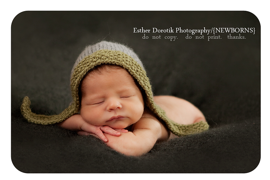 photograph-of-newborn-boy-posing-on-blanket-with-hat