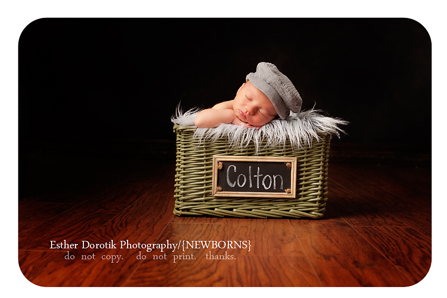 newborn-photo-of-baby-boy-laying-in-basket-with-name-wearing-newsboy-hat