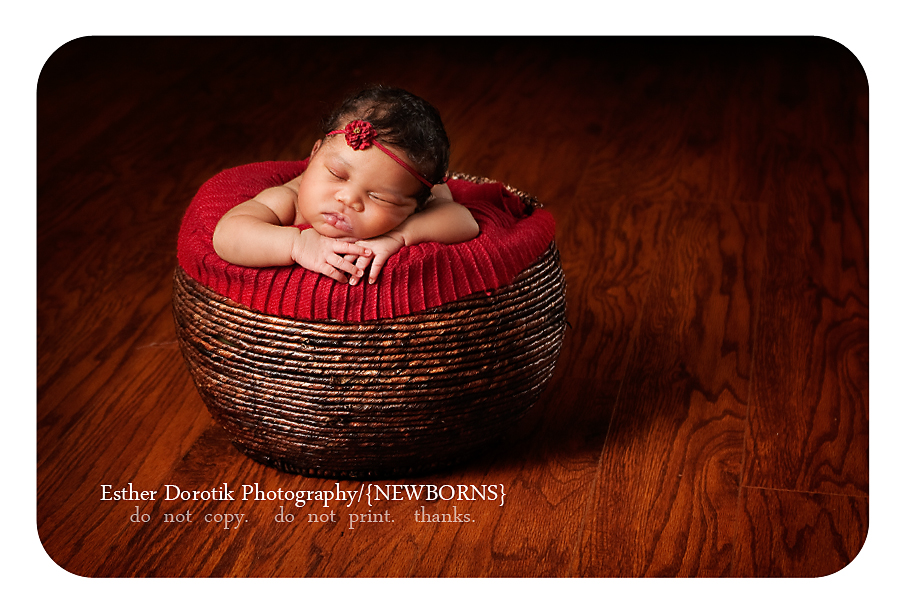 newborn-baby-with-red-headband-laying-on-red-blanket-in-wood-basket
