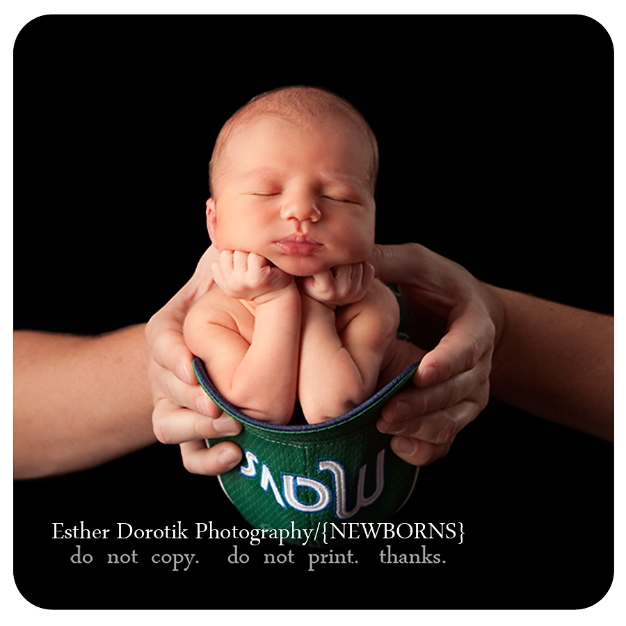 newborn-photograph-of-baby-boy-with-hands-under-chin-in-baseball-hat