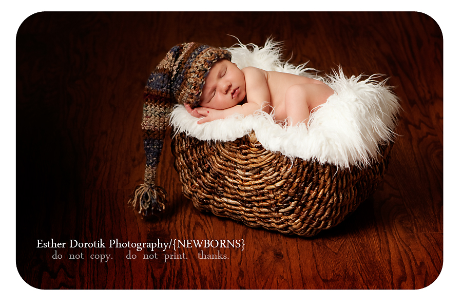 photo-of-newborn-baby-laying-in-basket-with-fur-and-stocking-hat