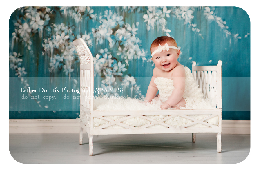 laughing-baby-girl-photographed-on-chic-baby-bed-with-ruffle-pants
