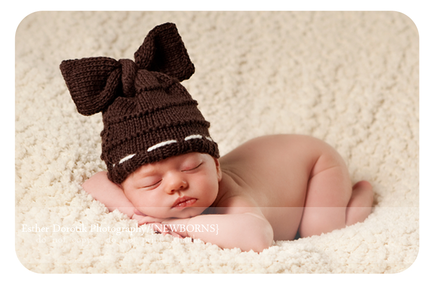 picture-of-newborn-baby-girl-posing-on-cream-blanket-with-brown-bow-hat