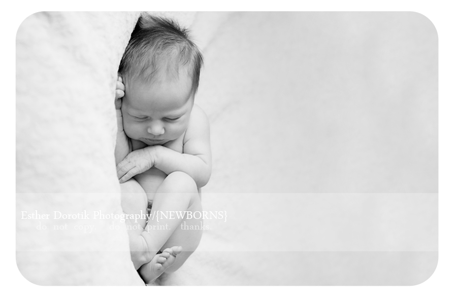 newborn-girl-laying-on-bean-bag-in-black-and-white