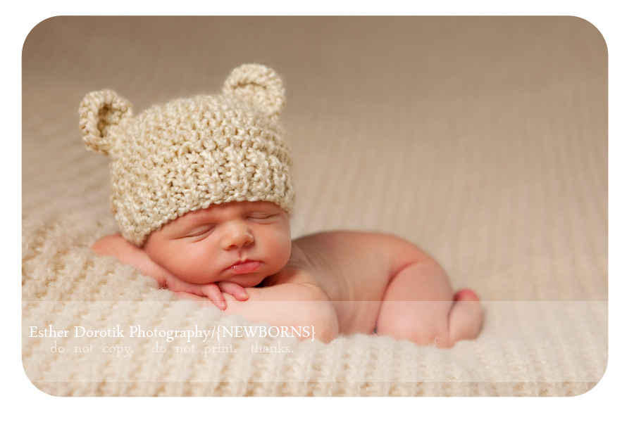 newborn-photography-of-baby-boy-posed-on-blanket-with-bear-hat-on