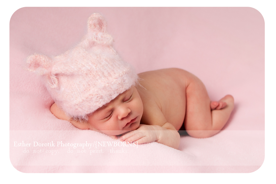 Dallas-newborn-posing-on-pink-blanket-with-kitten-hat