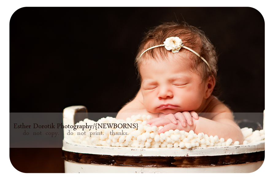 newborn-photography-of-baby-girl-posed-on-blanket-with-yellow-headband