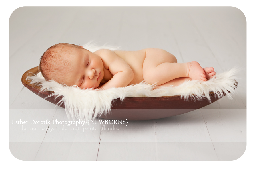 newborn-baby-laying-in-wood-bowl-with-fur-on-white-floor