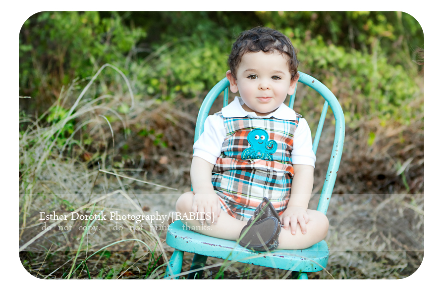 infant-photographer-captures-one-year-old-sitting-on-antique-chair-in-field