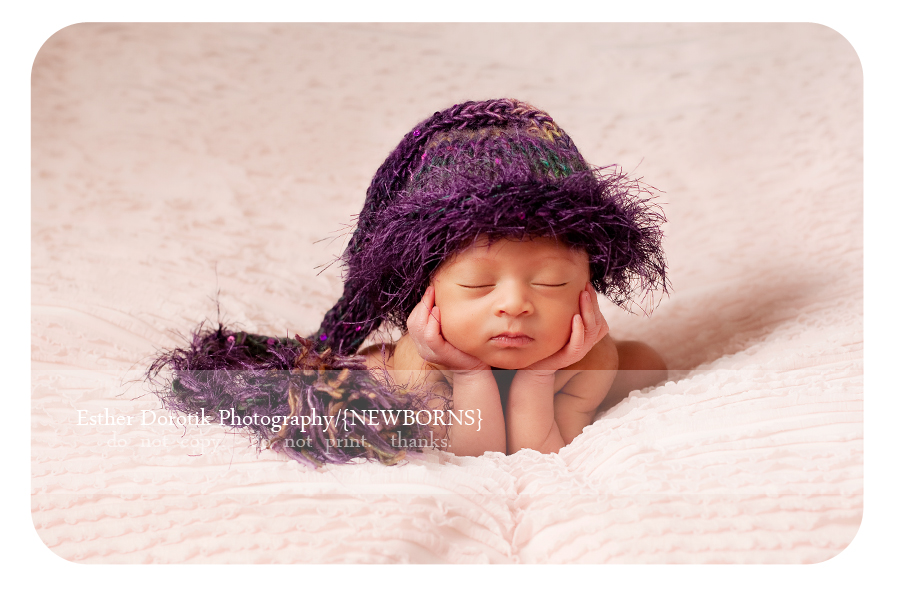new-born-baby-with-her-hands-under-chin-and-knit-hat-by-best-newborn-photographer