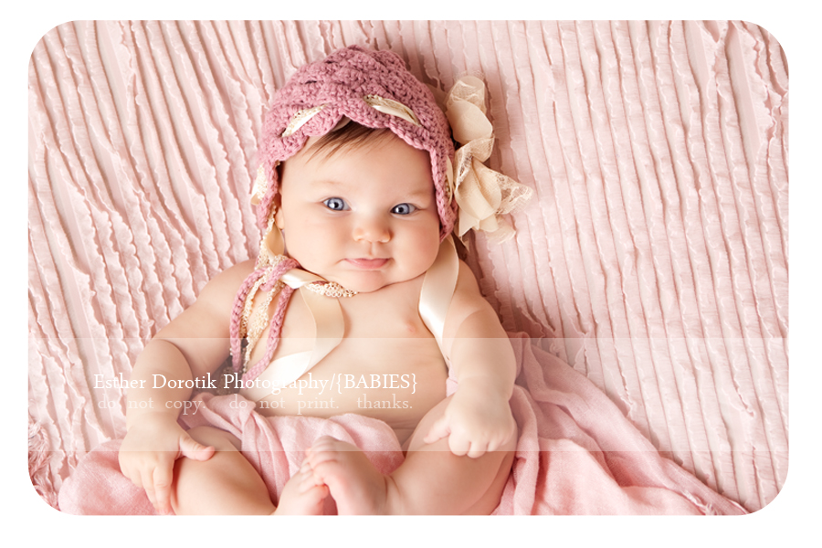 3-month-old-photography-of-baby-girl-laying-on-blanket-with-pink-bonnet-on