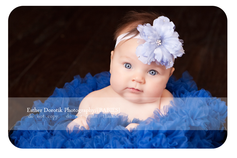 4-month-old-baby-girl-sitting-in-blue-petticoat-with-blue-headband-taken-by-infant-photographer