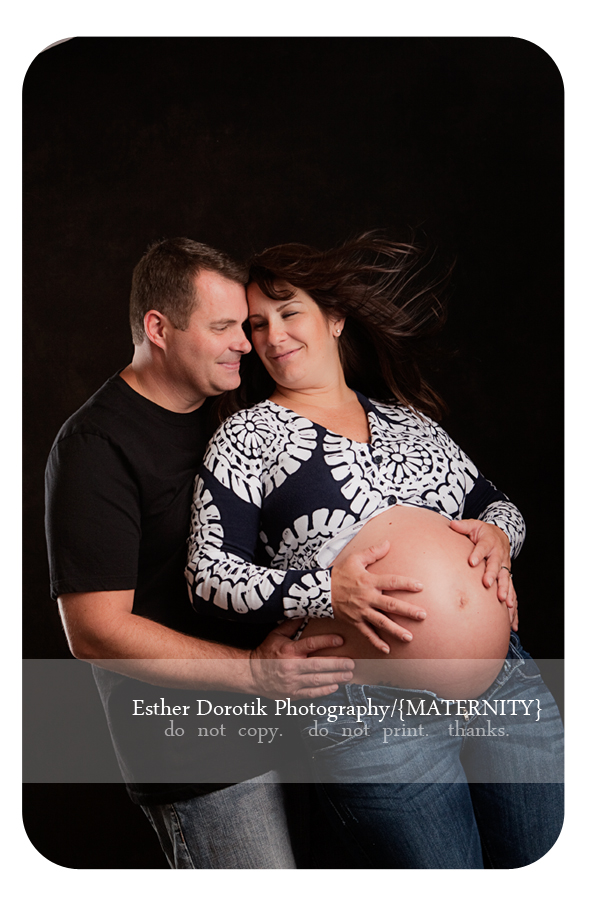 couple-expecting-newborn-photographed-in-studio-with-wind-machine-holding-belly