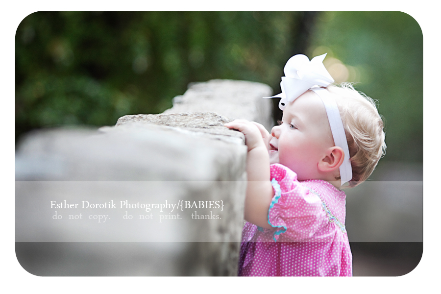 infant-girl-photographed-looking-over-stone-wall-outdoors-with-family-photographer-in-Dallas