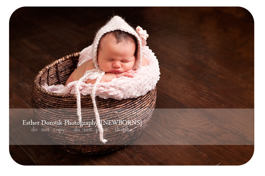 newborn-baby-girl-laying-in-round-basket-with-pink-bonnet-hat-on-taken-by-Dallas-Photographer