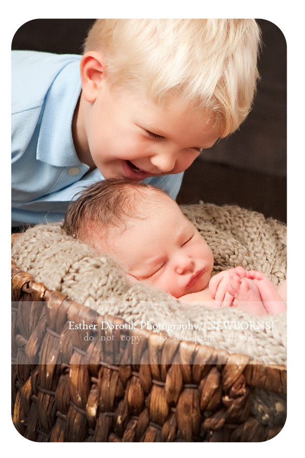 newborn-boy-being-kissed-by-big-brother-taken-by-Plano-sibling-photographer