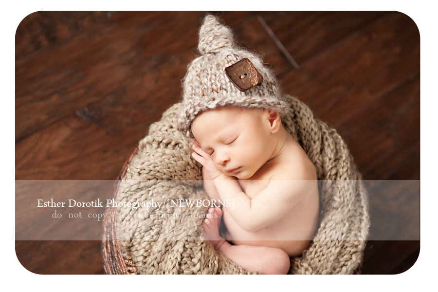 new-born-baby-laying-in-basket-with-brown-button-knit-hat-with-hands-beside-his-face