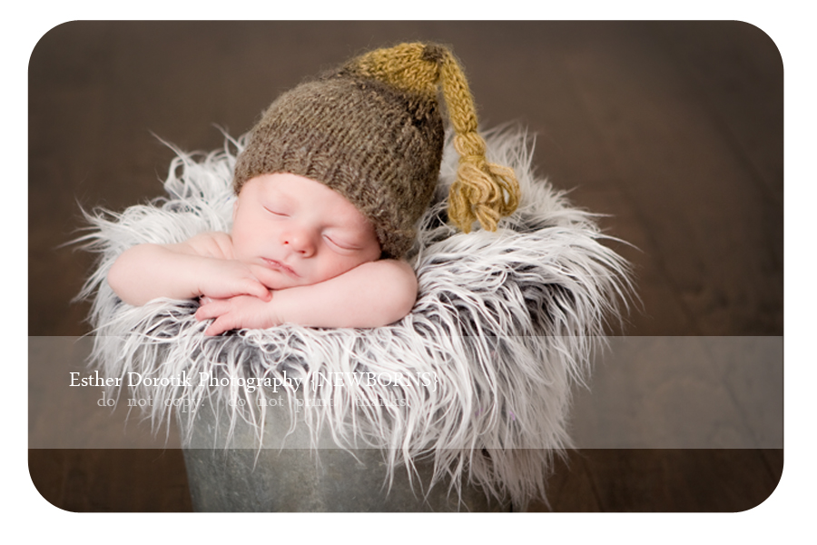 timeless-newborn-picture-of-baby-boy-in-galvanized-bucket-with-knotty-hat-and-grey-fur