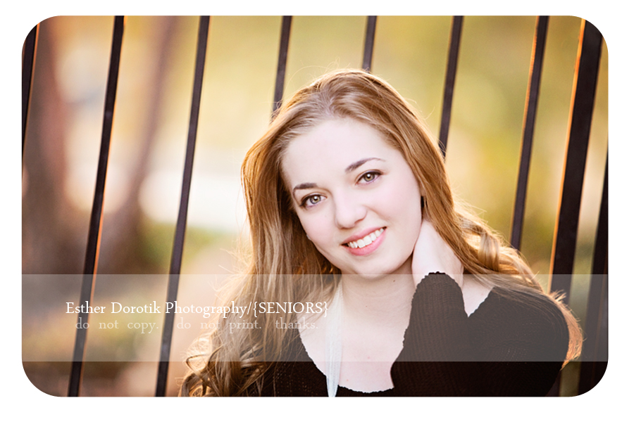 close-up-of-beautiful-Flower-Mound-High-school-girl-sitting-in-front-of-iron-gate