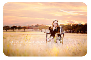 family-photographer-captures-senior-in-field-sitting-in-chair-with-beautiful-sunset