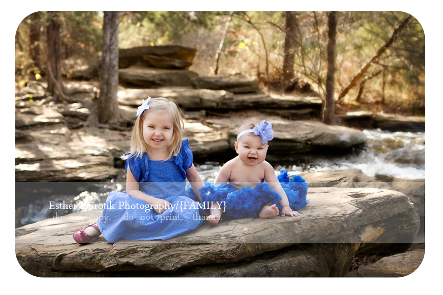 picture-of-sweet-sisters-sitting-on-rocks-in-creek-by-Plano-baby-photographer