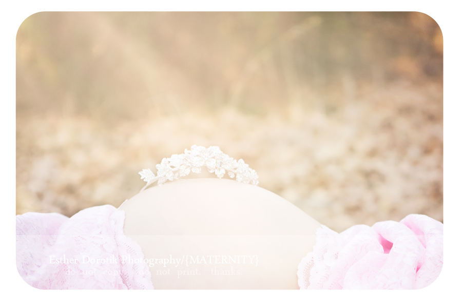 bright-and-sunlit-image-of-maternity-session-outdoors-with-crown-on-tummy-and-sunflare