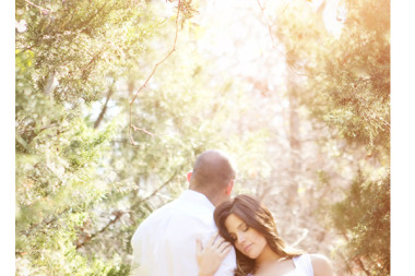 bright-maternity-photo-of-mom-holding-dad-in-trees-with-sunflare-taken-by-Plano-photographer