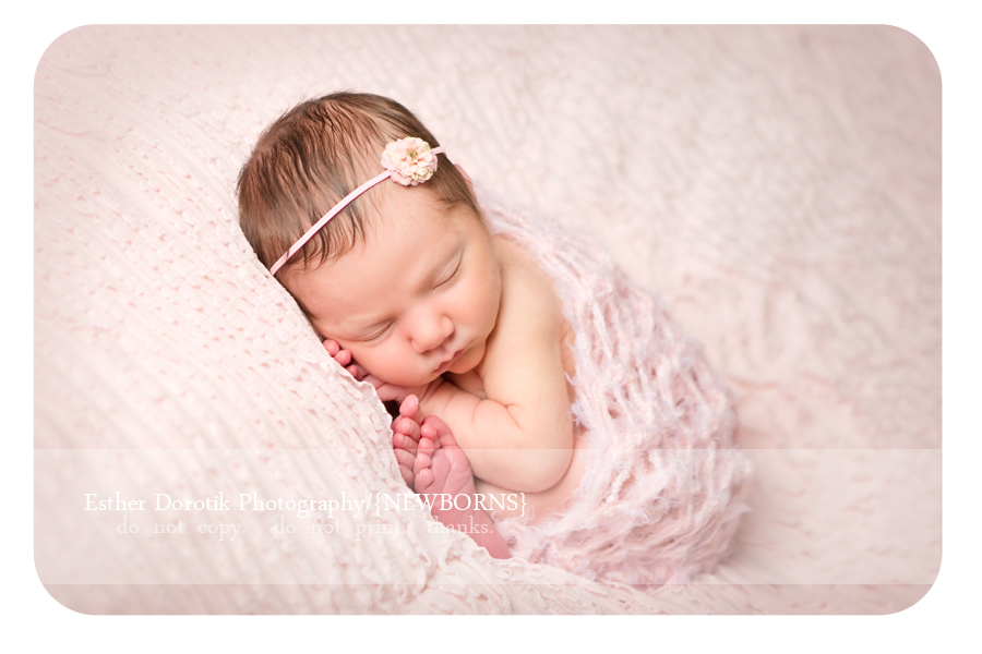 Fort-worth-newborn-photography-capturing-little-girl-in-taco-pose-with-pink-knit-wrap-and-headband