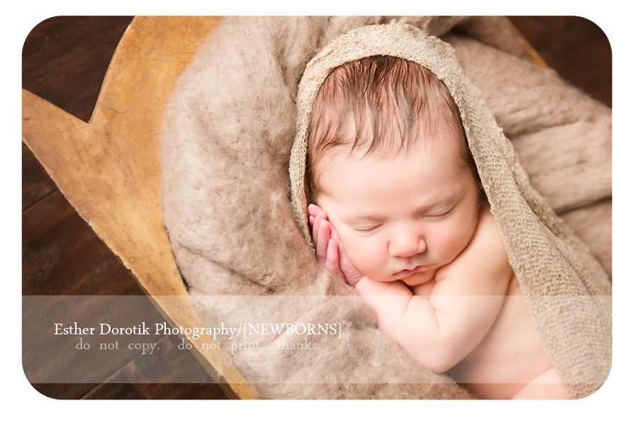 unique-newborn-photographer-captures-baby-girl-in-basket-with-hands-by-face-by-Grapevine-baby-photographer