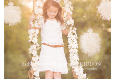 photo-of-6-year-old-girl-standing-in-swing-with-pompoms-hanging-from-tree-by-Dallas-Child-photographer