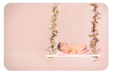 newborn-baby-girl-laying-on-swing-with-pink-flowers-by-Dallas-Fort-Worth-newborn-baby-photographer