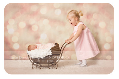 2-year-old-sister-pushing-newbonr-sister-in-pram-stroller-with-Christmas-lights-by-Dallas-newborn-photographer