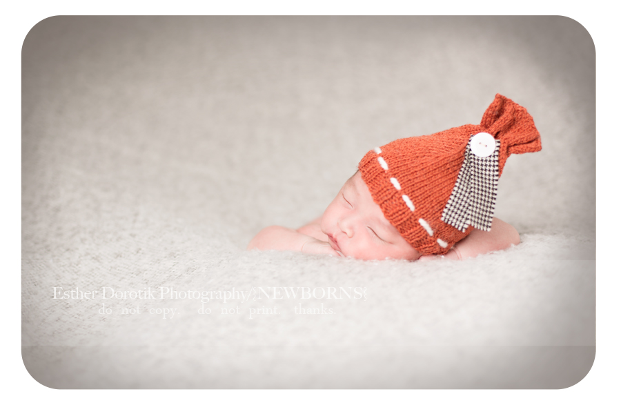 newborn-baby-boy-posed-on-gray-blanket-with-orange-hat-by-Coppell-newborn-photographer