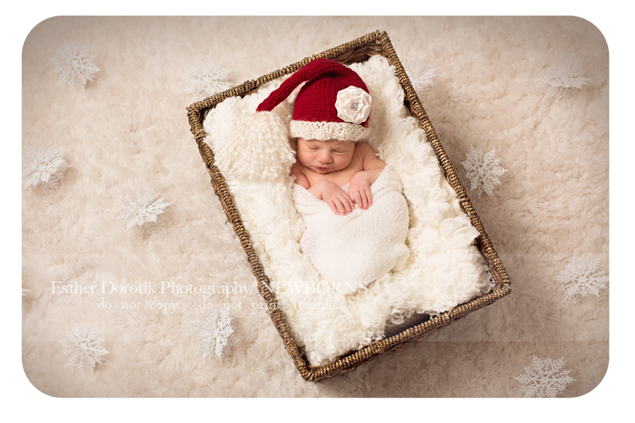newborn-baby-girl-wrapped-in-knit-with-red-santa-hat-on-and-snowflakes-by-Valley-Ranch-photographer