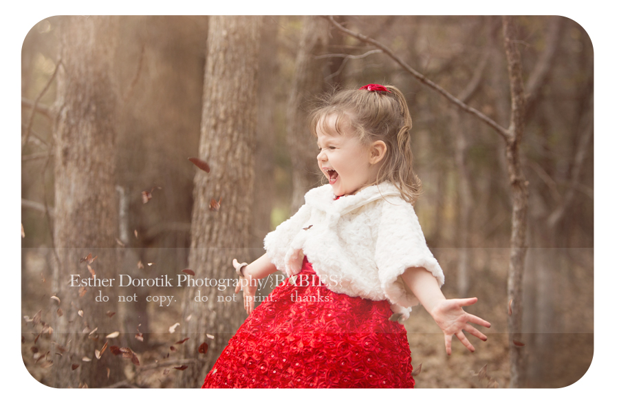 picture-of-happy-little-girl-in-Christtmas-dress-throwing-leaves-by-lifestyle-Dallas-child-photographer
