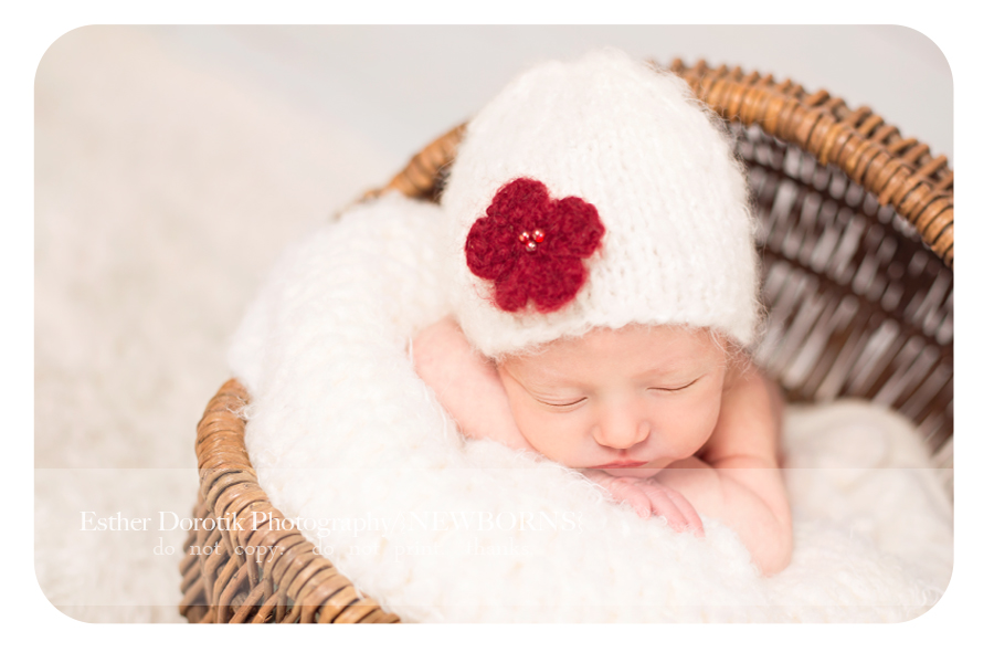newborn-picture-of-baby-girl-laying-on-creme-blanket-with-white-hat-and-red-flower-by-Dallas-newborn-photographer