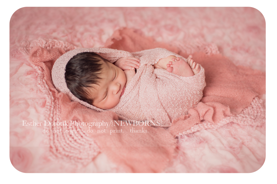 new-born-baby-girl-wrapped-in-pink-knit-on-layered-blanket-taken-by-Irving-newborn-photographer