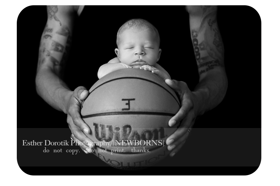 black-and-white-picture-of-newborn-boy-laying-on-basketball-held-in-dad