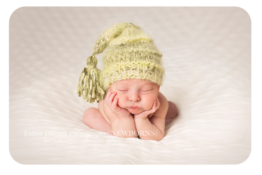 picture-of-newborn-in-frog-pose-with-green-hat-on-by-Dallas-newborn-photographer