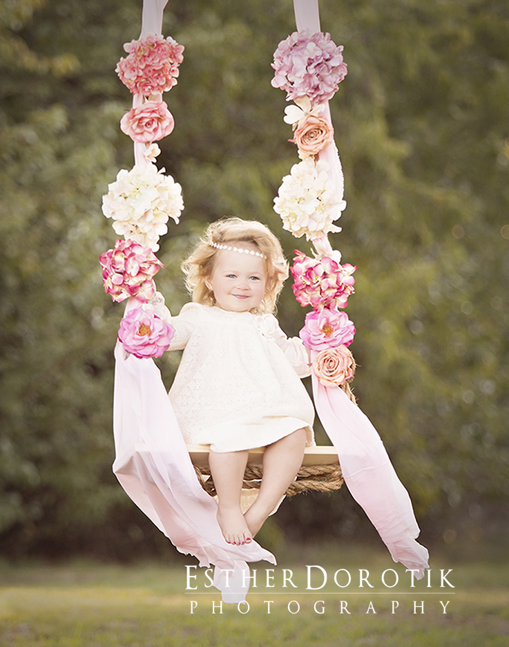 picture-of-2-year-old-girl-swinging-with-flowers-on-it-by-Dallas-baby-photographer