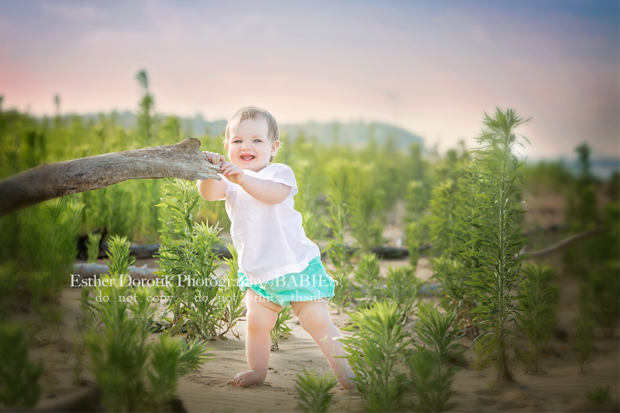 one-year-old-photo-of-little-girl-at-the-lake-standing-by-branch-by-Frisco-baby-photographer