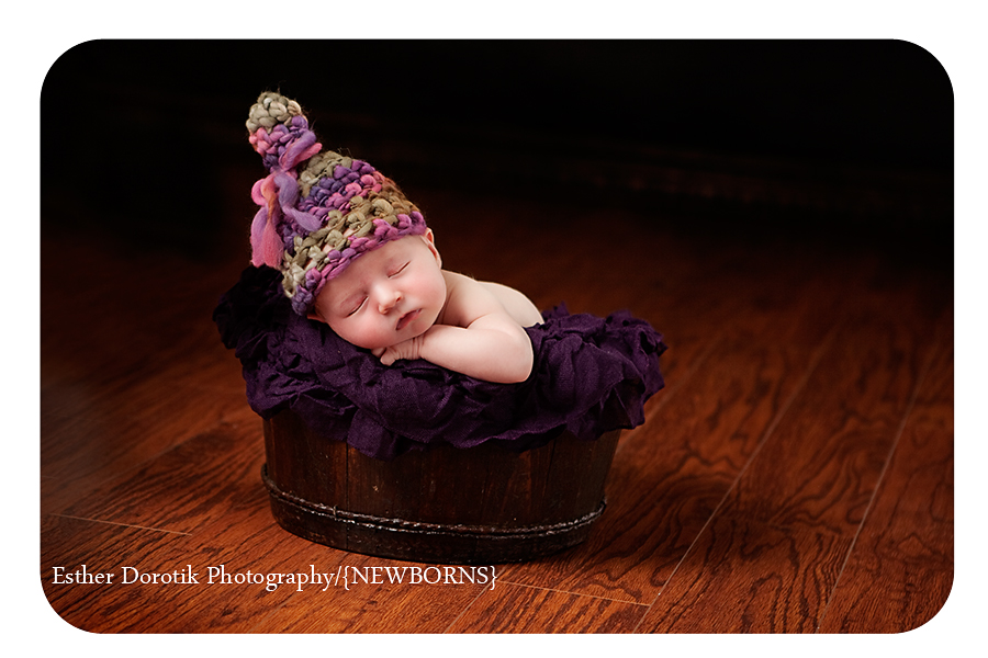 newborn-girl-laying-in-wooden-bucket-with-hat-photographed-by-esther-dorotik