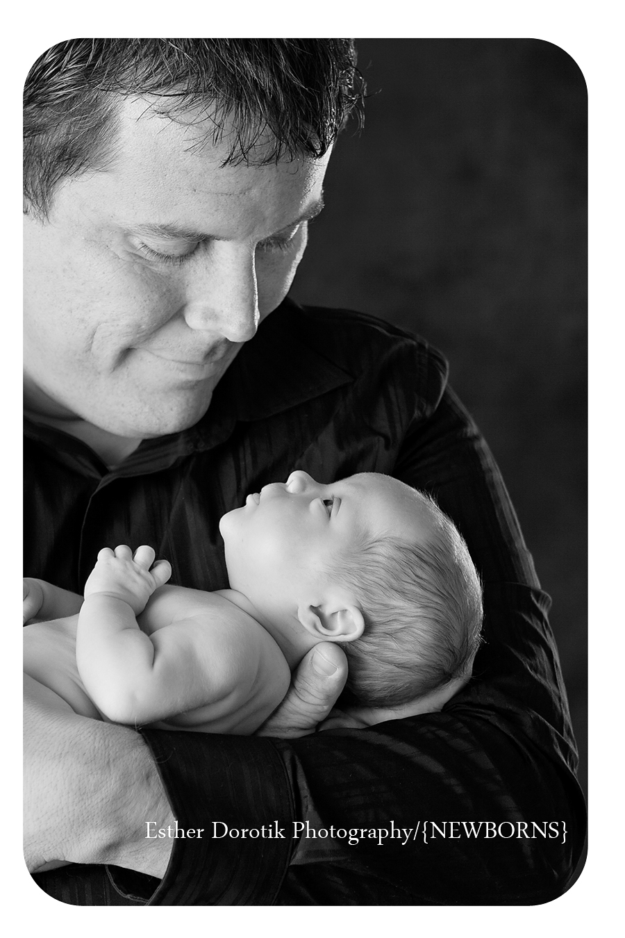 black-and-white-photograph-of-newborn-looking-up-at-daddy
