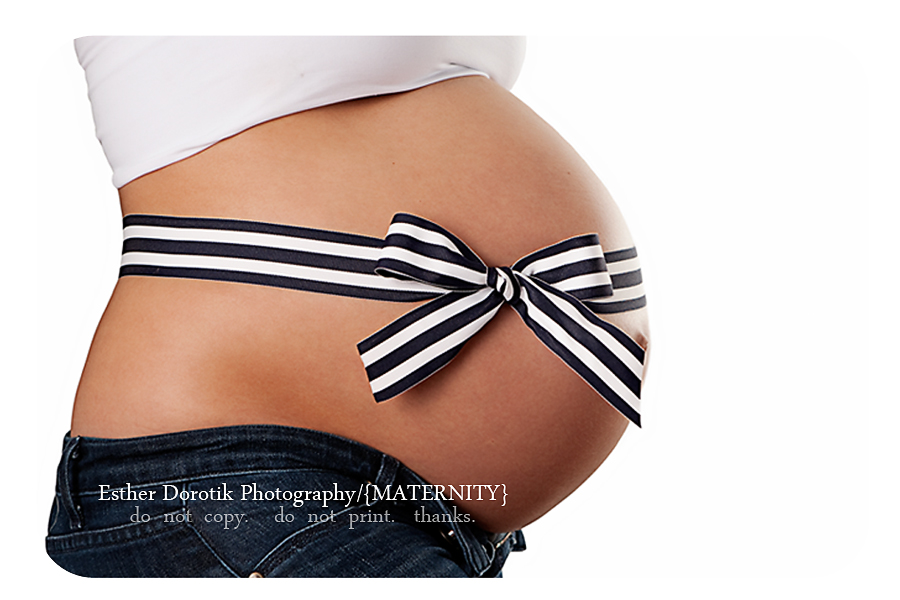 maternity-photo-of-belly-with-ribbon-wrapped-around-against-white-background-in-dallas
