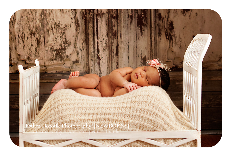 newborn-baby-girl-laying-in-bed-with-headband-on