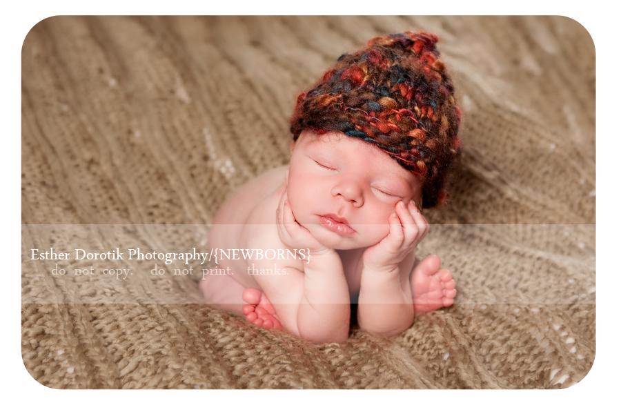 newborn-boy-with-hands-under-chin-on-cream-blanket