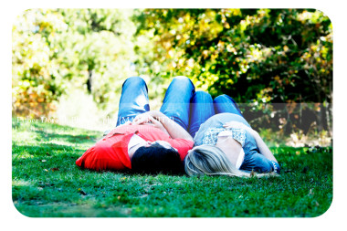 pregnancy-photograph-of-mom-and-dad-laying-in-grass-field-captured-by-Dallas-maternity-photographer