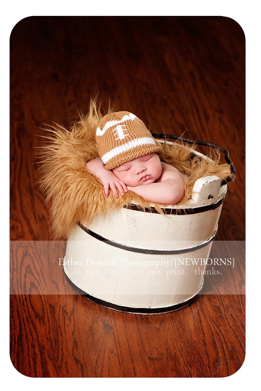 newborn-baby-in-cream-basket-with-football-hat-in-fur-captured-by-best-newborn-photographer