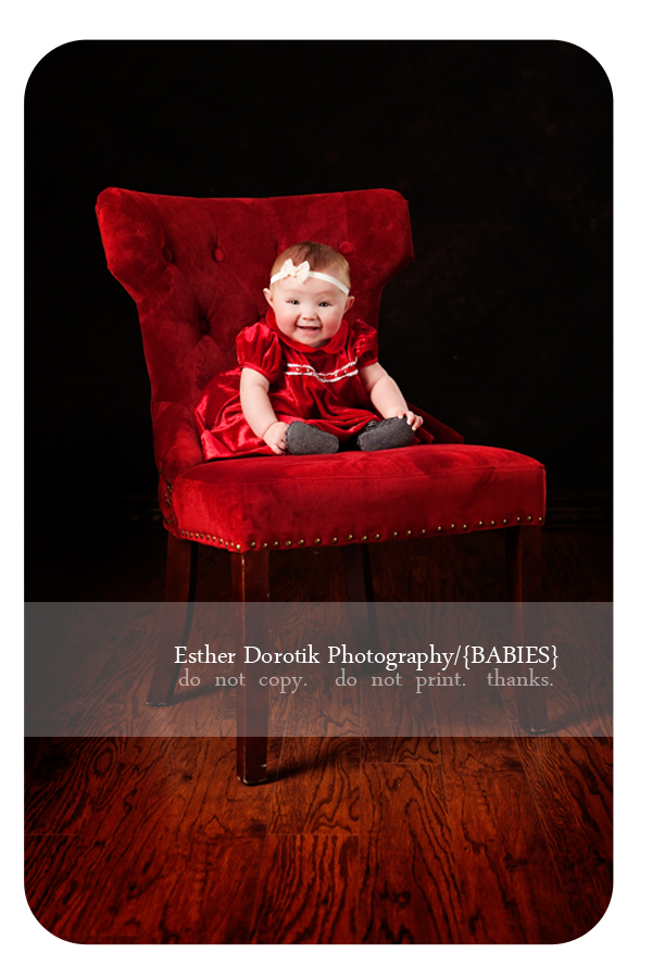 picture-of-6-month-old-girl-in-Christmas-dress-sitting-on-red-chair
